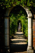 Classical Archway in garden of old English house with statue and greenery behind