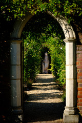 Classical Archway at old English house with statue and greenery behind