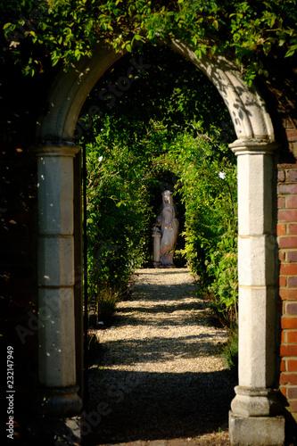 Klasyczny Archway w ogrodzie starego domu angielskiego z posągu i zieleni za