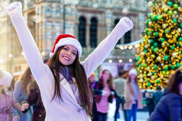 Glückliche Frau mit roter Weihnachtsmütze hat Spaß auf einem Weihnachtsmarkt mit Eislaufbahn