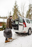 A man puts garbage bags in the trunk of a car. On a frosty winter day on a background of snow-covered woods and house. - 232156563