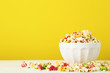 Colorful popcorn in bowl on yellow background