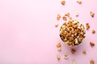 Caramel popcorn in bowl on pink background