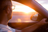 young man driving a car at sunset. Travel concept - 232160180
