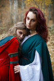 Two girls in medieval dress in the autumn forest. - 232161325