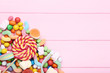 Sweet candies and lollipops on pink wooden table