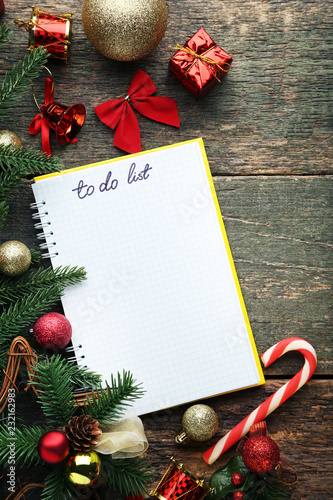 To do list in notepad with christmas decorations on wooden table