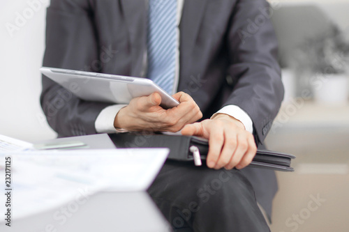 Leinwanddruck Bild close up.Businessman with leather briefcase with digital tablet