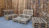 Rustic, self-made benches and a table made of euro pallets in front of a wooden wall - 232172589