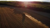 Aerial view of combine harvesting weat on a field near a farm at sunset - 232174707
