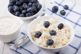 Cottage cheese in a white bowl with berries of fresh blueberries - 232176987