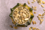 Fresh pepita seeds in hollowed pumpkin on gray marble background - 232180776