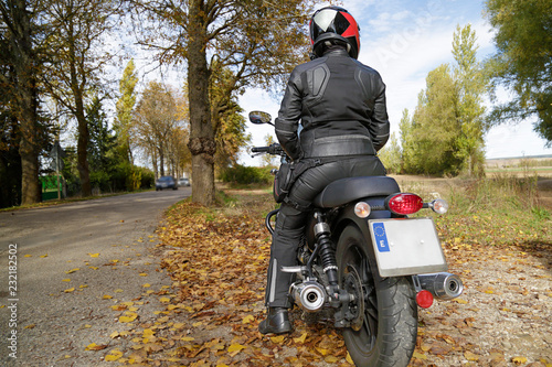 Rear view of a biker girl parked on the side of the road © Raquel Pedrosa