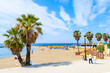 Leinwandbild Motiv MARBELLA TOWN, SPAIN - MAY 12, 2018: Couple of tourists walking on coastal promenade along beach in Marbella seaside town. Southern Spain is popular holiday destination in Europe.