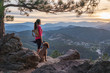 A hispanic woman is hiking with a dog, at sunset, in the Rocky Mountains near Denver, Colorado, USA