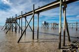 les pilotis d'un ponton sur un rivage de Vendée avec les célèbres cabanes de pêcheur - 232188713
