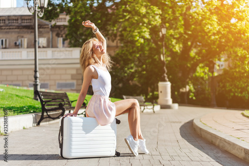 Poster Girl traveler with a white suitcase