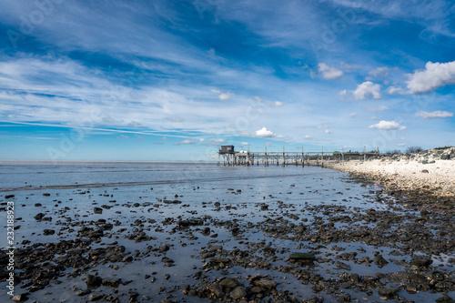 Foto Murales bord de mer en Vendée avec des galets et une maison sur pilotis au loin