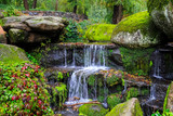 A picturesque cascade waterfall among large moss covered stones in the landscape Sophia Park, Uman, Ukraine,  Autumn Sofievsky - 232189170