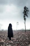 Woman in black cape in moody landscape. - 232193957