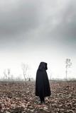 Woman in black cape in moody landscape. - 232193965