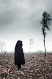 Woman in black cape in moody landscape. - 232193968