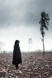 Woman in black cape in moody landscape. - 232193972