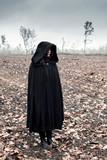 Woman in black cape in moody landscape. - 232193974