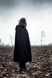 Woman in black cape in moody countryside. - 232193980