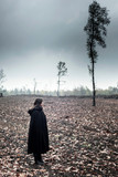 Woman in black cape in moody countryside. - 232193981