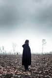 Woman in black cape in moody countryside. - 232193984