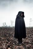 Woman in black cape in moody landscape. - 232193985