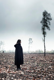 Woman in black cape in moody countryside. - 232193987