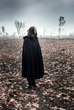 Woman in black cape in moody countryside. - 232193989