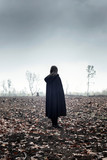 Woman in black cape in moody countryside. - 232193995