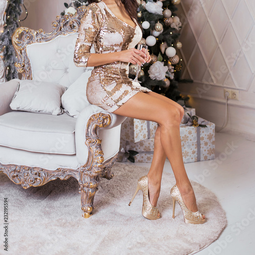 Luxurious woman sitting on a chair on the back of an expensive Christmas background
