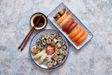Asian food assortment. Various sushi rolls placed on ceramic oriental style plates. Soy souce and chopsticks on sides. Grungy dark background with copy space. © Dash