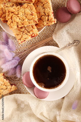 Poster Purple macaroons, biscuits and a white cup with a saucer and a spoon