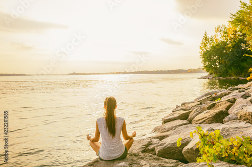 Poster Yoga class outside in nature park by lake river shore. Woman sitting in lotus pose meditating by the water in morning sun flare sunrise. Meditation wellness.