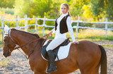 Girl equestrian rider riding a beautiful horse  in the rays of the setting sun. Horse theme - 232203739