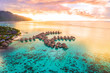Leinwanddruck Bild - Luxury travel vacation aerial of overwater bungalows resort in coral reef lagoon ocean by beach. View from above at sunset of paradise getaway Moorea, French Polynesia, Tahiti, South Pacific Ocean.