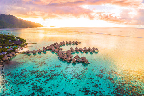 Leinwanddruck Bild Luxury travel vacation aerial of overwater bungalows resort in coral reef lagoon ocean by beach. View from above at sunset of paradise getaway Moorea, French Polynesia, Tahiti, South Pacific Ocean.