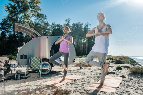 Leinwanddruck Bild One foot. Loving healthy couple standing on one foot while doing morning yoga near their mobile home