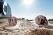 Leinwanddruck Bild - Meditating on sand. Couple of yoga professionals feeling relieved while meditating together on sand near river