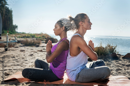 Leinwanddruck Bild Healthy couple. Healthy loving couple breathing slowly while meditating together in nature near the river