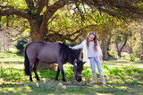 Cute little girl and pony in a beautiful park - 232209361