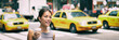 New York city commute - Asian business woman walking to work in the morning commuting drinking coffee cup on NYC street with yellow cabs in the background banner. People commuters lifestyle.
