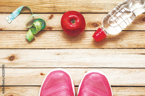 Sport sneakers, centimeter, apple and a bottle of water on a wooden background. Top view