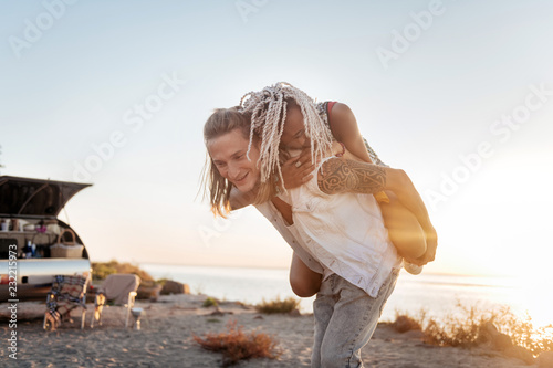 Leinwanddruck Bild Hugging tight. Young appealing stylish woman with dreadlocks hugging her strong handsome man tight