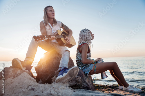 Leinwanddruck Bild Playing guitar. Blonde-haired athletic stylish man with tattoo on hand playing the guitar near his woman